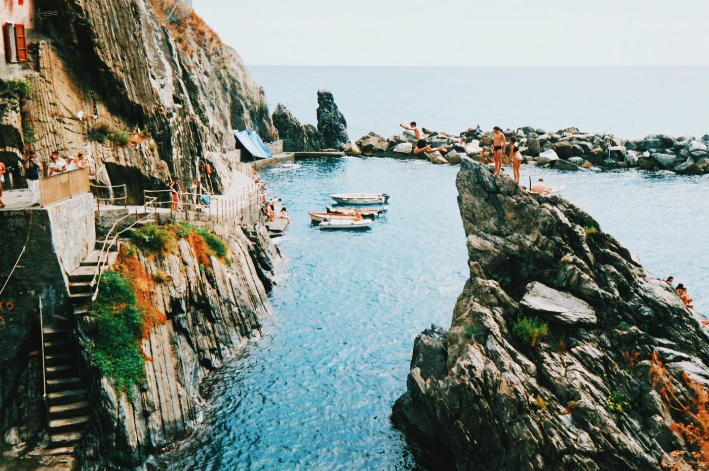 man jumping into ocean - swimming in Manarola, Cinque Terre
